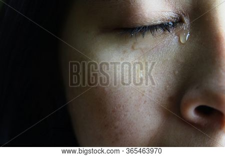 Close-up Half Face Of Asian Woman Crying With Tears, Isolated On Dark Background. Concepts Of Emotio