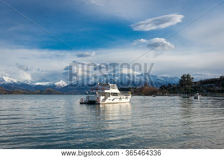 Winter Mountain Landscape With Lake And Fishing Boats. Lake Wanaka Fishing Boats With Snow Capped Mo