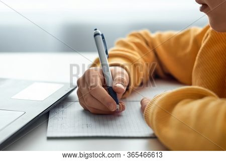 Hand Of A Child With A Pen Close-up Doing Homework. The Concept Of Online Learning, Distance Learnin