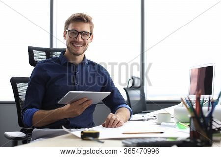 Young Modern Business Man Working Using Digital Tablet While Sitting In The Office.