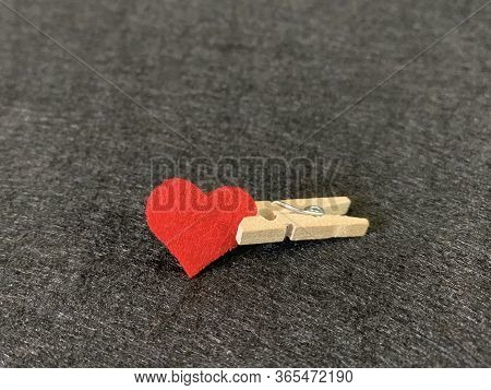 Red Heart Clamped Clothespin, On A Dark Background. Sign Of The Heart In Slavery. Concept: Heart Dis