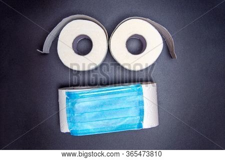 Toilet Paper Rolls Are Laid Out In The Form Of An Emoticon With A Blue Medical Face Mask. On A Black