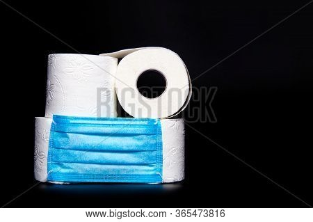 Rolls Of White Toilet Paper With A Blue Medical Face Mask Are On A Black Background. Coronavirus Out