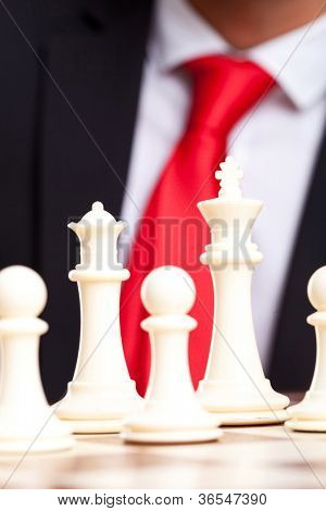 White chess king, queen and pawns in front of business man