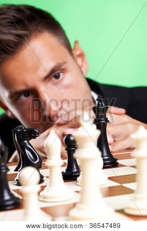 Young business man thinking at a chess strategy and looking at his king