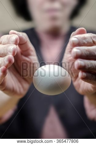 Hands Of A Woman Perform A Magic Trick With The Egg. Levitation Of The Egg In The Air, Selective Foc