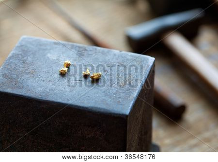 Gold nuggets on a old anvil, with tools in background.