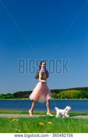 Young Woman With Her Dog. Puppy White Dog Is Running With It's Owner. Concept About Friendship, Anim