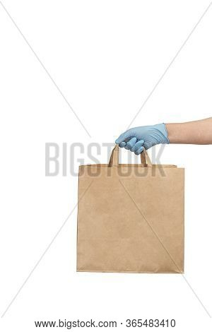 Delivery Man In Medical Gloves Holding Paper Craft Bag With Food. Coronavirus Food Delivery. Volunte