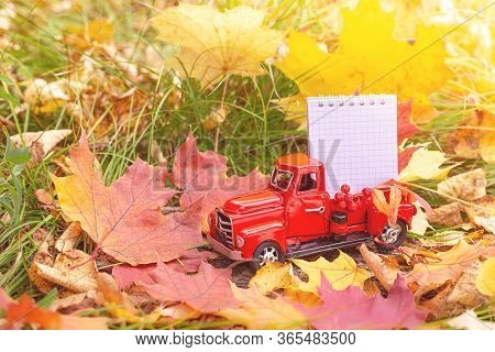 Izhevsk, Russia, September 14, 2019. Retro Car Toy Carrying Notebook In Autumn Forest. Red Car In Au