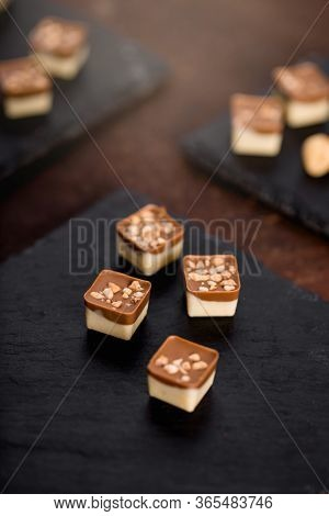 Still Life Of Various Delicious Chocolate Pralines On Dark Textured Background