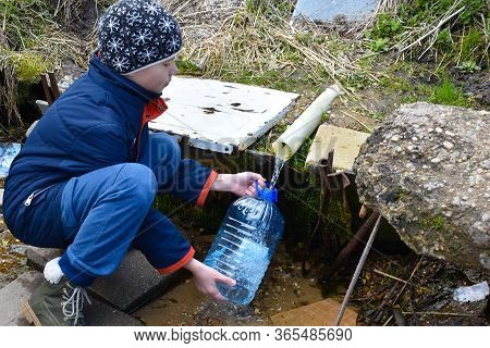 Water Natural Source. A Boy Pours Water In The Source. The Child Goes Over The Clear Water Spring. T