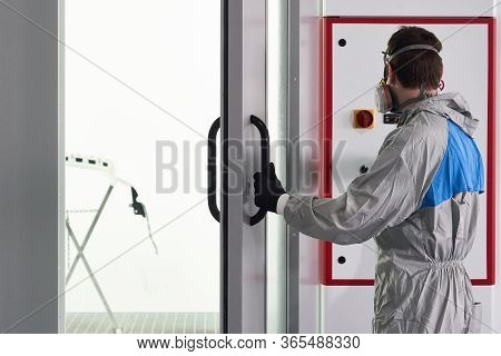 Mechanic Entering Painting Booth In Repair Auto Service For Painting Bumper Of A Car With Sprayer
