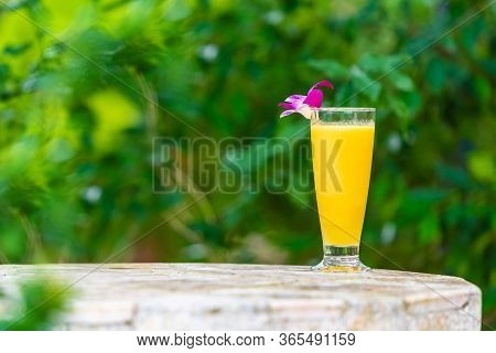 A Mango Smoothie In A Glass Stands On A Marble Table, Decorated With An Orchid Flower, On The Tropic