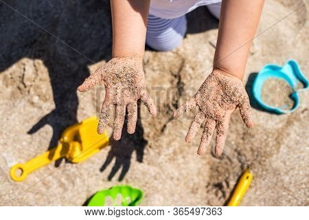 Close Up Hands Of Happy Girl Playing In Sand On The Beach.