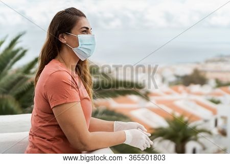 Mature Woman Wearing Medical Face Mask And Gloves Standing On Home Terrace - People Quarantine For P