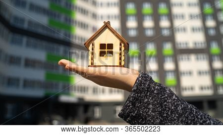 Close Up Of Small Wooden House In Womans Hand On Background Of Built House. Concept Of Purchasing Ne