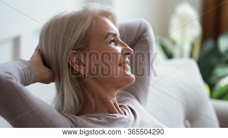 Calm Mature Woman Relax On Couch Daydreaming