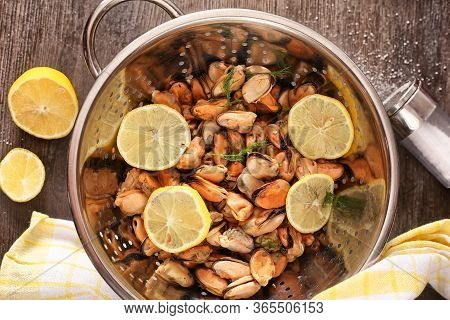 Ready Mussel On A Blue Plate And Board With Seasoned Butter And Lemons On A Dark Wooden Surface. Mus