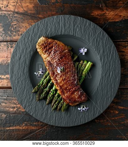 Grilled Sirloin Beef Steak On Fried Asparagus Served On Black Slate Plate With Rosemary Flowers