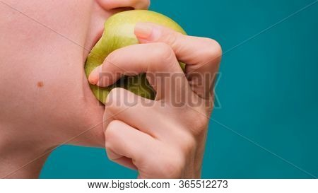 Healthy Eating And Healthy Teeth Or Diet, Young Woman Bites A Fresh Apple On A Green Screen Close-up