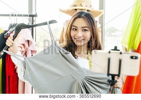 Beauty Female Fashion Vlogger Presenting Grey Dress To Cellphone And Smiling Showing Clothes Selling