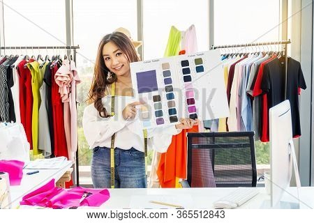 Asian Woman Designer Standing Smiling With Holding Show Fabric Color Sample At The Designer Desk In
