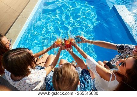 Top View Of Of Friends Clinking Glasses With Fresh Colorful Cocktails Sitting By Swimming Pool On Su