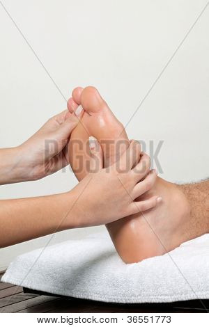 Close up of female masseuse massaging man's foot