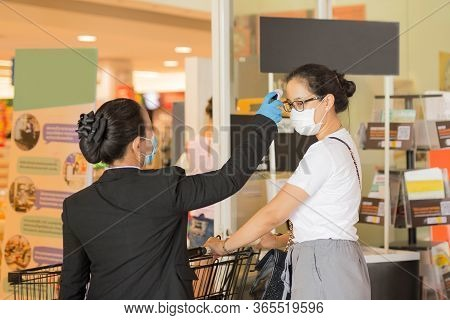 Grocery Staff With Checking Temperature Of Customer For Codvid-19 Protection