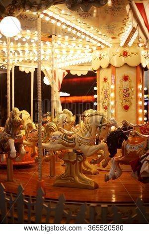 Beautiful Horse Christmas Carousel In A Holiday Park. Horses On A Fairground Carousel. Merry-go-roun