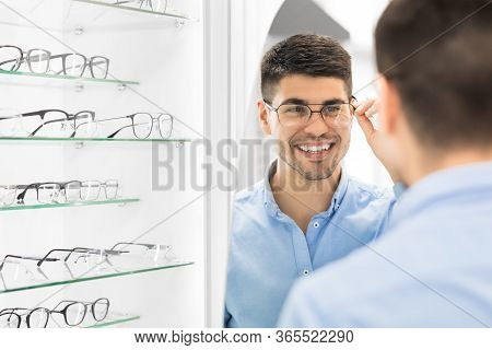 Choosing Glasses Concept. Portrait Of Handsome Bearded Guy Picking New Specs At Optical Shop, Lookin