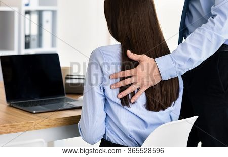 Sexual Harassment At Workplace. Businessman Harassing Female Coworker Touching Her Shoulder Working