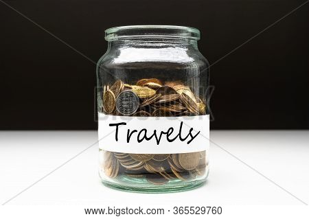 Coins In A Jar With Travels Text On A White Label. Savings Abstract Concept. Copy Space.