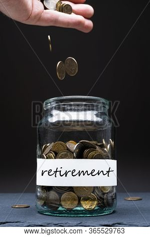 Coins In A Jar With Retirement Text On A White Label. Caucasian Man Throwing Money From Above. Savin