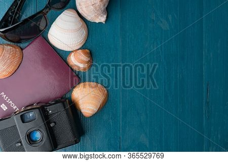 Passport, Vintage Film Camera, Sunglasses And Seashells On A Blue Wooden Background. Summer Travel A