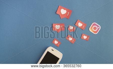 Minsk, Belarus-april 25, 2020: Instagram Hearts Like Over Dark Blue Background With Smartphone. A Pi
