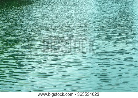 Blue Texture Of The Surface Of The Water Pond Lake River, Small Waves On The Water Surface, Light Br