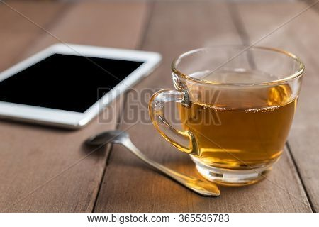 Close Up Hot Tea Cup On Wood Table With Tea Spoon And Tablet Shot On Moning Time Witn Sun Ray Backgr