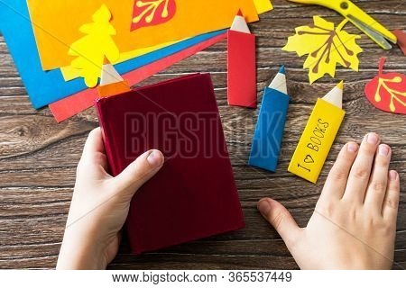Child Holds Multi-colored Bookmarks Origami Pencil Made Of Paper New School Year On A Wooden Table.