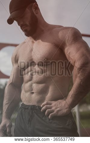 Handsome Strong Young Man With Beard Wearing Black Cap With Perfect Abdominal Muscles Standing Outdo