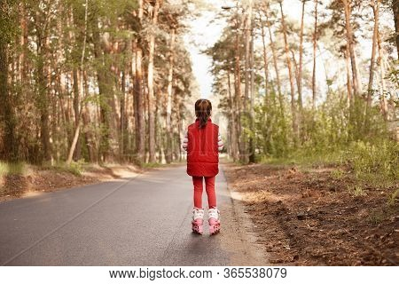 Picture Of Active Energetic Little Girl Wearing Red Suit, Rollerskating During Holidays, Enjoying Na