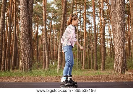 Outdoor Shot Of Attractive Woman Dresses Casual Attire Rollerblading In Forest During Her Weekend. L
