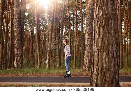 Side View Of Pretty Girl Posing In Forest, Surrounded With Trees, Rollerblading On Asphalt Road, Wea