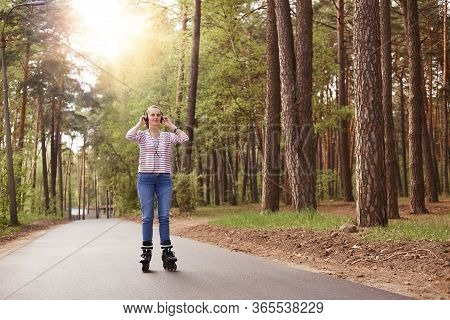 Attractive Sporty Woman Wearing Casual Attire Rollerblading And Listening To Music, Keeping Hands On