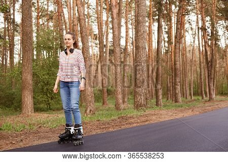Attractive Slim Woman Wearing Jeans And Striped Shirt,having Headphones Around Neck, Rollerblading I