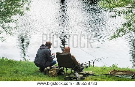 A Fisherman Catches Fish On The River On A Warm Spring Day. A Man Catches Fish Sitting On A Chair.