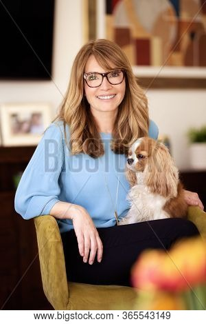 Smiling Mature Woman Sitting In Armchair With Her Puppy At Home