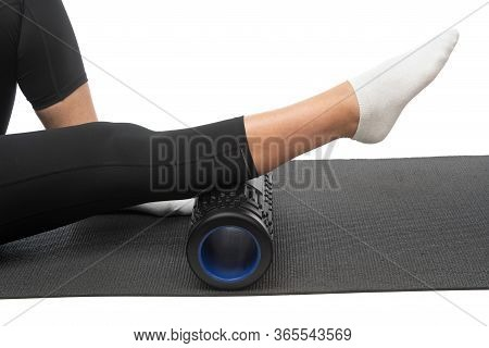 A Middle-aged Woman On A Myofascial Roller Does A Leg Shin Massage On A White Background.