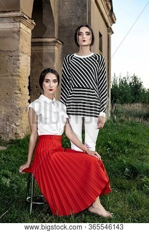 Outdoor Fashion Portrait Of Two Young Beautiful Women Wearing Fashionable Clothes Posing On The Stre